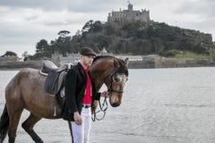 Красивый человек, всадник мужской лошади идя с его лошадью на пляже, нося традиционной плоской крышке, белых брюках, красной руба Стоковое фото RF
