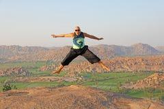 Красивый человек высокого прыжка Солнечные очки в Hampi, скачки облыселого человека нося высоко на холме Anjaneya, виске Hanuman  стоковая фотография