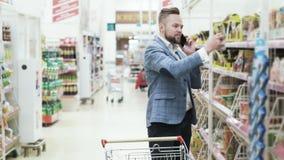 Красивый человек в белой рубашке говорит на телефоне и покупая бакалеях в супермаркете сток-видео