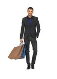 Красивый человек в костюме с хозяйственными сумками Стоковые Изображения RF