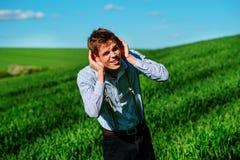 Красивый человек в природе пробует услышать что-то с установкой стоковая фотография