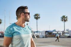 Красивый человек в солнечных очках смотря отсутствующий outdoors Стоковые Фотографии RF