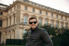 Красивый человек в хаки куртке и солнечных очках сидит на барде Улыбка Гая и имеет tourits остатков стоковая фотография rf