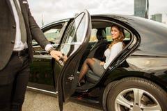 Красивый человек держа автомобильную дверь для красивой коммерсантки стоковое изображение