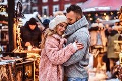 Красивый человек и очаровательная девушка прижимаясь и наслаждаясь тратящ время совместно пока стоящ на ярмарке зимы на a стоковое фото rf