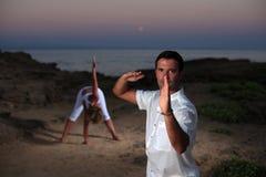 Красивый человек на пляже meditating Стоковые Фото