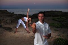 Красивый человек на пляже meditating Стоковое Изображение