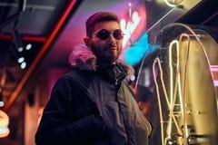Красивый человек нося пальто и солнечные очки с руками в карманах, стоя в ночи на улице стоковое фото rf