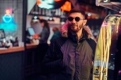 Красивый человек нося пальто и солнечные очки с руками в карманах, стоя в ночи на улице стоковые изображения