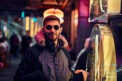 Красивый человек нося пальто и солнечные очки с руками в карманах, стоя в ночи на улице стоковая фотография rf