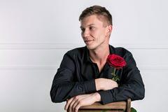 Красивый человек нося черную рубашку держа розу и получая готовую романтичную дату стоковая фотография