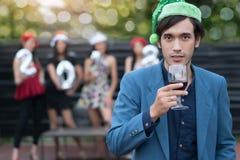 Красивый человек нося шляпы Санта с бокалом вина удерживания на стоковое фото rf