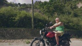 Красивый человек путешествуя на мотоцикле на летнем дне Мотоцикл катания старшего человека на тропическом ландшафте гористых мест акции видеоматериалы