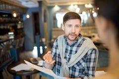 Красивый человек разговаривая с коллегой о бумагах Стоковое Изображение
