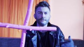 Красивый человек со стильными волосами отрезанными в танцах кожаной куртки держа розовый крест видеоматериал