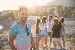Красивый человек стоя на пляже с его усмехаться друзей Стоковые Изображения