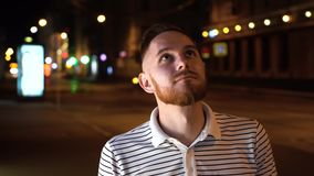 Красивый человек с бородой смотрит вверх и после этого в камере Одетый в striped рубашке и стойке поло на улице вечером акции видеоматериалы