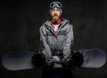 Красивый человек с красной бородой нося полное удерживание оборудования сноуборд и смотря камеру, изолированную на темноте стоковые изображения rf