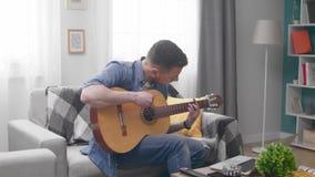 Красивый человек учит сыграть гитару с помощью онлайновому учебнику акции видеоматериалы