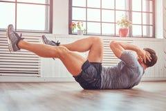 Красивый человек фитнеса в футболке и шортах делая подбрюшные тренировки на поле дома стоковое изображение rf