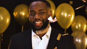 Красивый чернокожий человек подмигивая к камере на партии под падая confetti, flirting сток-видео