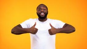 Красивый чернокожий человек усмехаясь уверенно, показывающ большие пальцы руки вверх на желтой предпосылке стоковое фото