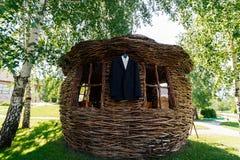 Красивый черный костюм ` s groom и белая рубашка висят на сплетенном gazelo Стоковое Изображение RF