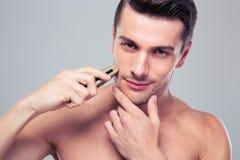 Красивый человек брея с электробритвой Стоковое фото RF