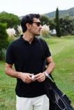 Красивый человек брюнет в стеклах с сумкой гольфа на плече держа шарик в руках Стоковое фото RF
