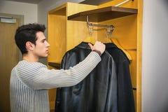 Красивый человек вися его пальто внутри его шкафа Стоковые Изображения RF