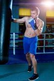 Красивый человек в голубых перчатках бокса тренируя на груше в спортзале Мужской боксер делая разминку Стоковые Изображения RF