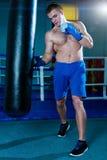 Красивый человек в голубых перчатках бокса тренируя на груше в спортзале Мужской боксер делая разминку Стоковая Фотография