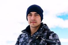 Красивый человек в зиме одевает против неба и смотреть камеру Стоковые Изображения