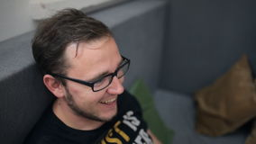 Красивый человек в стильных eyeglasses сидит на софе и улыбках счастливо акции видеоматериалы