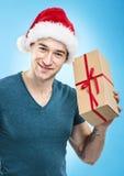 Красивый человек в шляпе santa - вручите подарочную коробку Стоковые Изображения RF
