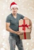 Красивый человек в шляпе santa - вручите подарочную коробку Стоковое Изображение RF