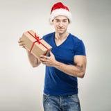 Красивый человек в шляпе santa - вручите подарочную коробку Стоковая Фотография