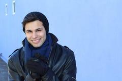 Красивый человек в mittens замерзает outdoors в дне холода зимы Стоковые Изображения