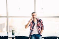 Красивый человек говорит на телефоне в офисе около больших окон Стоковое фото RF