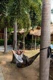 Красивый человек лежа на hammok и используя smartphone outdoors стоковое изображение rf