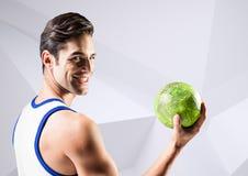 Красивый человек держа гандбол против белой предпосылки Стоковые Изображения