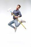 Красивый человек держа ролик краски и скакать изолированный на белизне стоковое фото rf