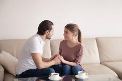 Красивый человек держа руки красивой женщины сидя внутри помещения, p Стоковая Фотография RF