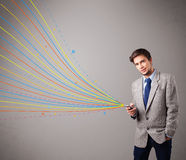 Красивый человек держа телефон с цветастыми абстрактными линиями Стоковые Изображения RF