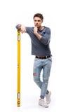 Красивый человек держа уровень здания изолированный на белизне, разнорабочем оборудует концепцию Стоковое фото RF