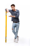 Красивый человек держа уровень здания изолированный на белизне Стоковое фото RF