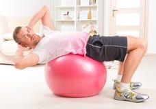 Красивый человек делать сидит поднимает на шарике Стоковое фото RF