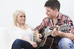Красивый человек играя гитару к милой девушке стоковая фотография