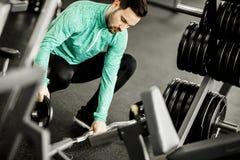 Красивый человек использует гантели в спортзале Стоковая Фотография RF