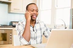 Красивый человек используя компьтер-книжку и имеющ телефонный звонок Стоковые Фото